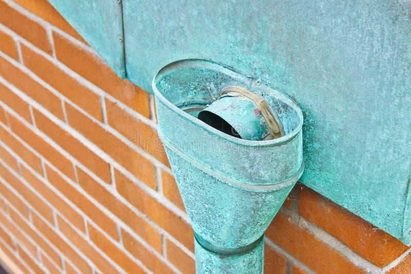 老生锈的铜落水管对砖墙 库存图片