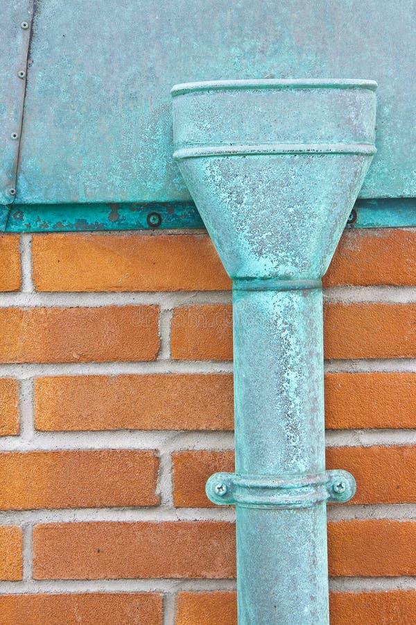 老生锈的铜落水管对砖墙 免版税库存图片