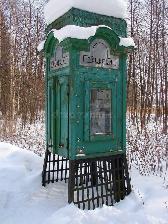 老电话亭在雪下的森林里 免版税库存图片