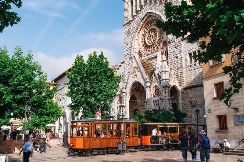 老电车在中世纪哥特式大教堂前面的索勒有巨大的圆花窗的,马略卡,西班牙 免版税库存图片