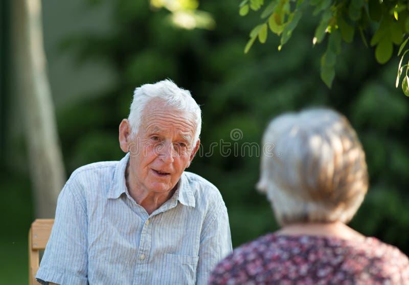 老男人和妇女谈话在公园 免版税库存照片