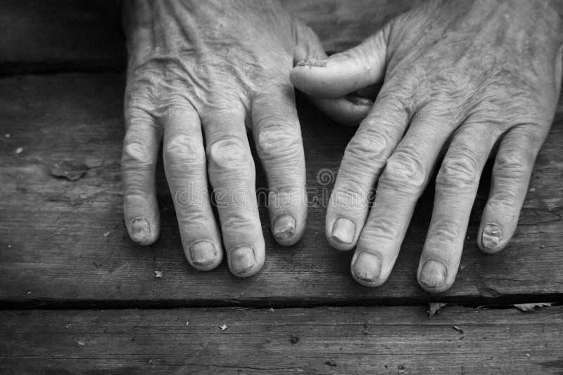 老病态的男性手,请求和要求的概念黑白照片古色古香的概略的木表面上的帮助 免版税库存照片