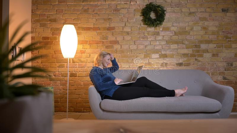 老白种人夫人画象说谎在沙发和高兴地与膝上型计算机一起使用在舒适家庭环境 图库摄影