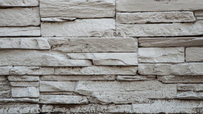 老白色铺石石头生锈的街道砖墙 免版税库存图片
