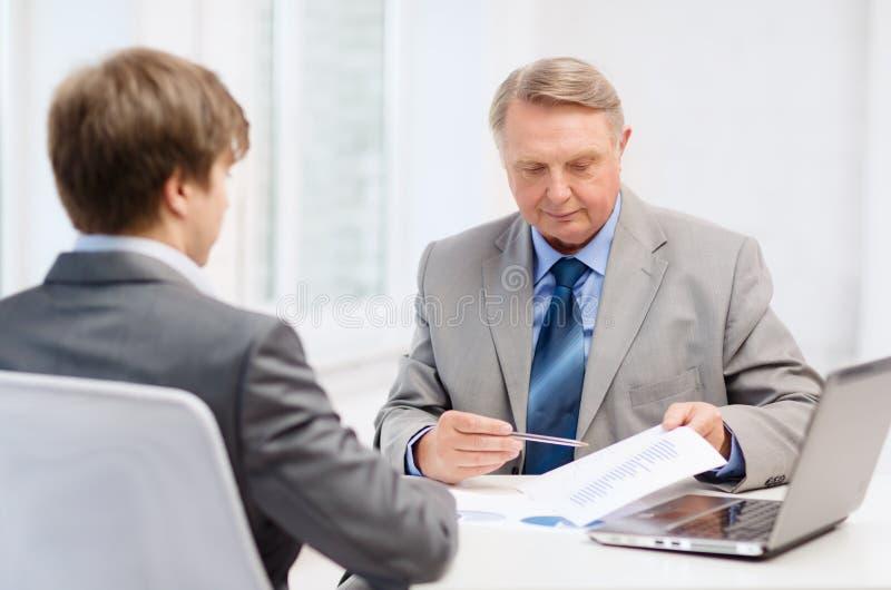 更老的人和年轻人开会议在办公室 免版税库存照片