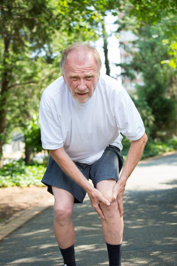 更老的人在痛苦中的掌握膝盖 免版税库存图片