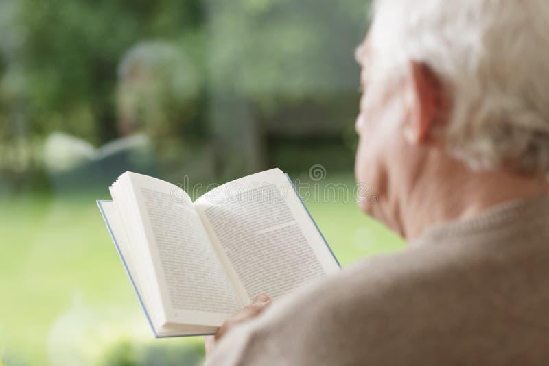 更老的人阅读书 库存照片