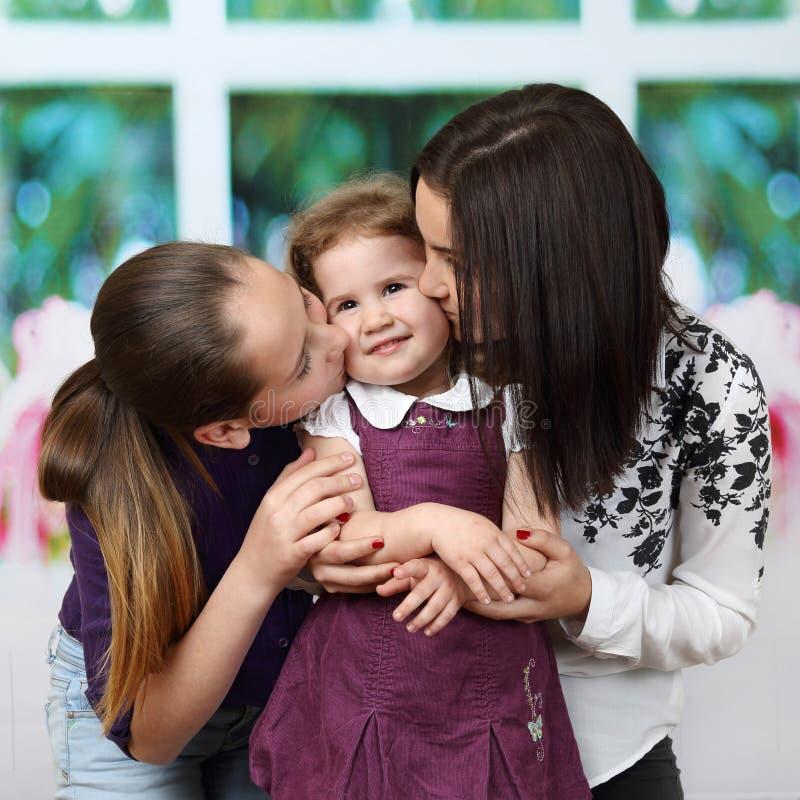 更老的女孩亲吻他们的一点siste 免版税库存图片