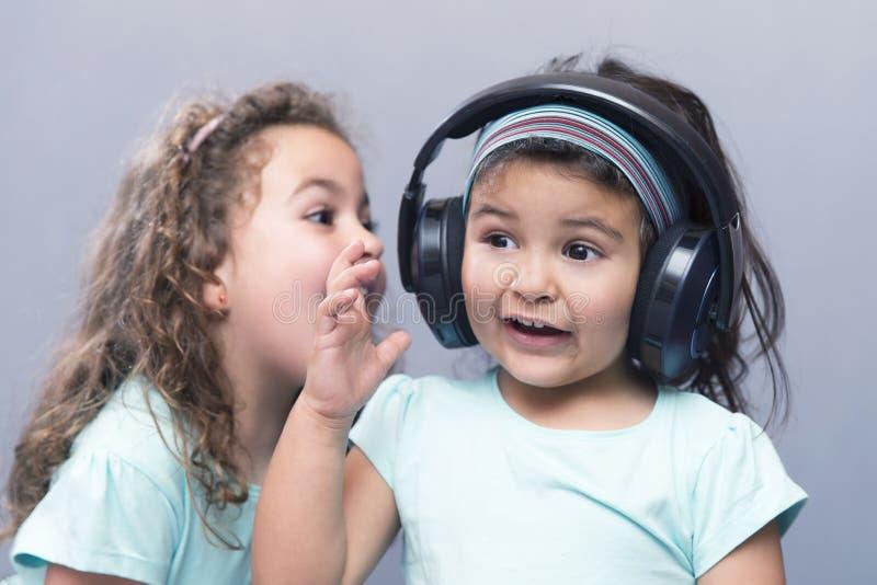 更老的姐妹尖叫对她的耳机的妹妹 免版税图库摄影