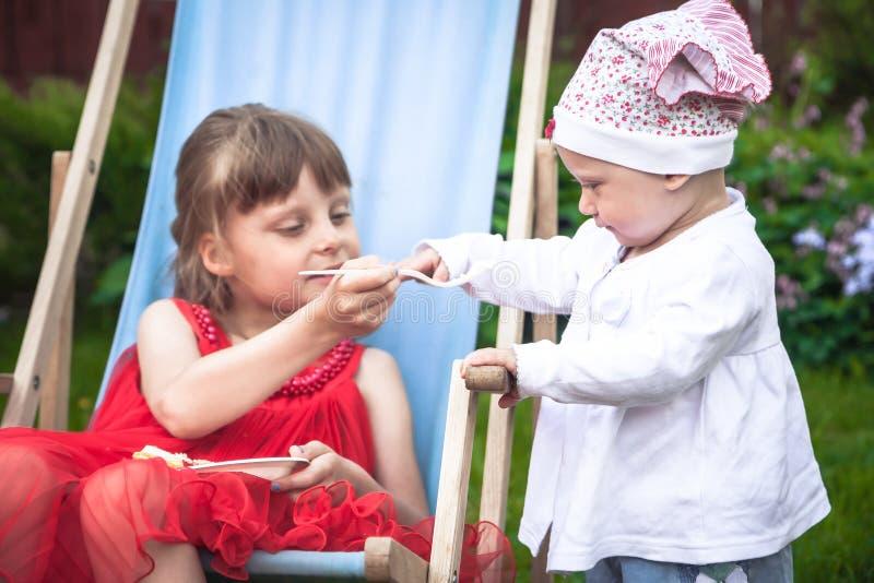 更老的姐妹照顾她的妹妹,当一起时使用户外在庭院里象征孩子的关心 免版税库存图片