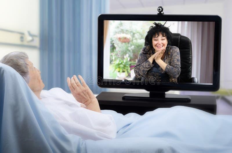 更老的患者有在医院病床上的录影闲谈 库存照片