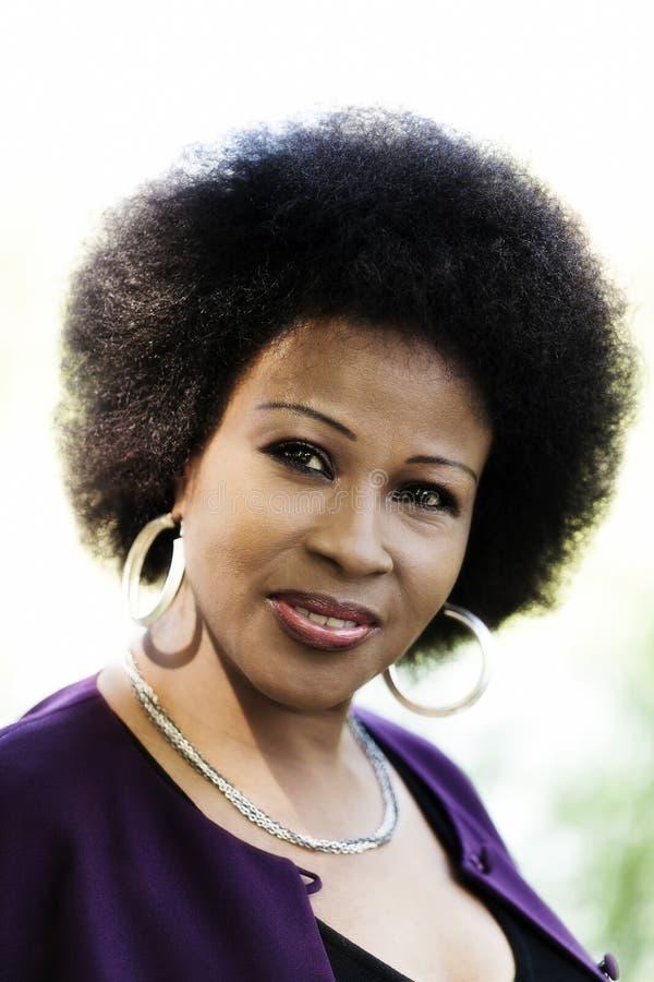 更老的非裔美国人的妇女室外画象紫色上面 免版税库存照片