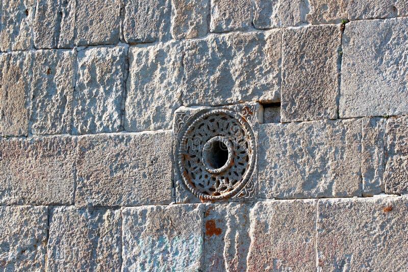 老石教会墙壁、圆的窗口和被盖的石灰石平板 库存图片