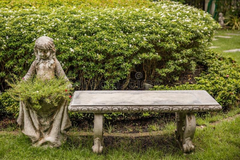 老石长凳和雕象与花瓶 库存图片