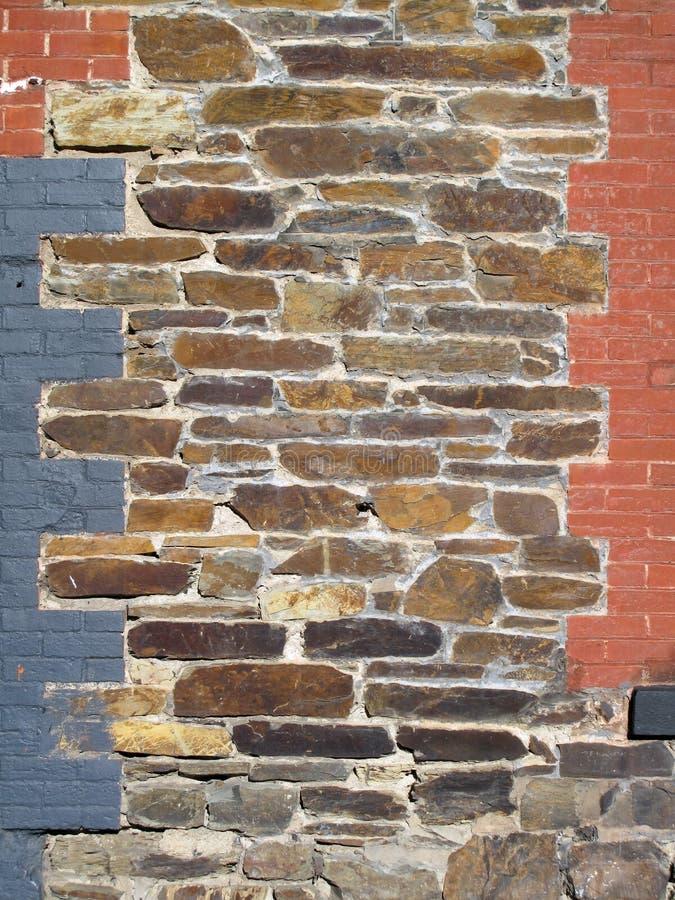 老石头和被绘的砖装饰了墙壁 库存图片