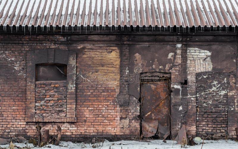 老砖有窗口的被放弃的在屋顶的房子和雪 库存图片