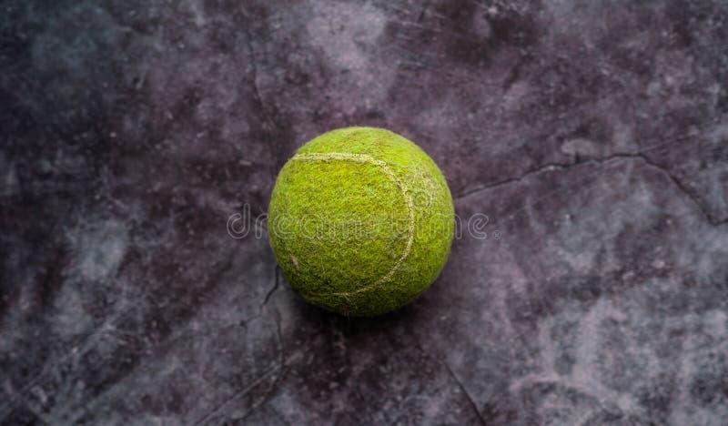 老破旧和多灰尘的绿色网球 免版税库存图片