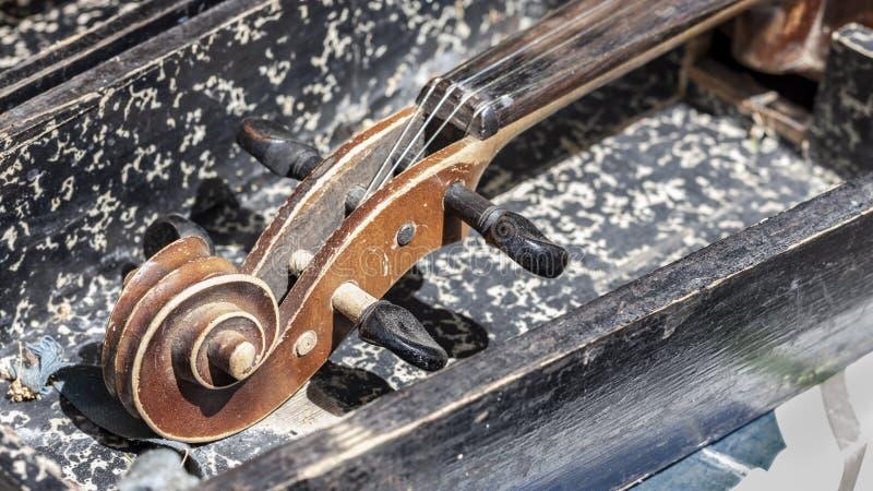 老破旧的葡萄酒小提琴 特写镜头与纸卷、脖子和pegbox的零件图象 免版税图库摄影
