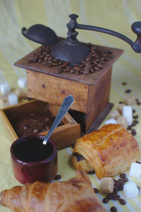 老磨咖啡器、杯子、匙子和糖 巧克力面包和新月形面包 免版税库存图片