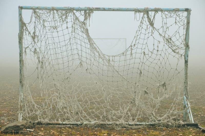 老空的被放弃的橄榄球场和门有被缠结的网的在一场轻的雾 库存图片