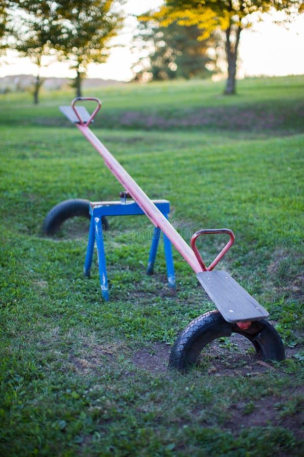 老空的金属跷跷板在室外儿童的游乐场 库存图片