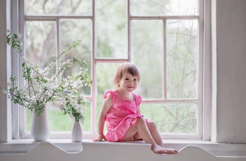 老窗台的美丽的小女孩与春天开花 免版税库存图片