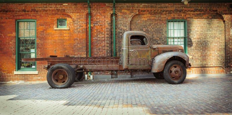 老站立反对砖瓦房的葡萄酒经典减速火箭的生锈的卡车惊人的看法  库存图片