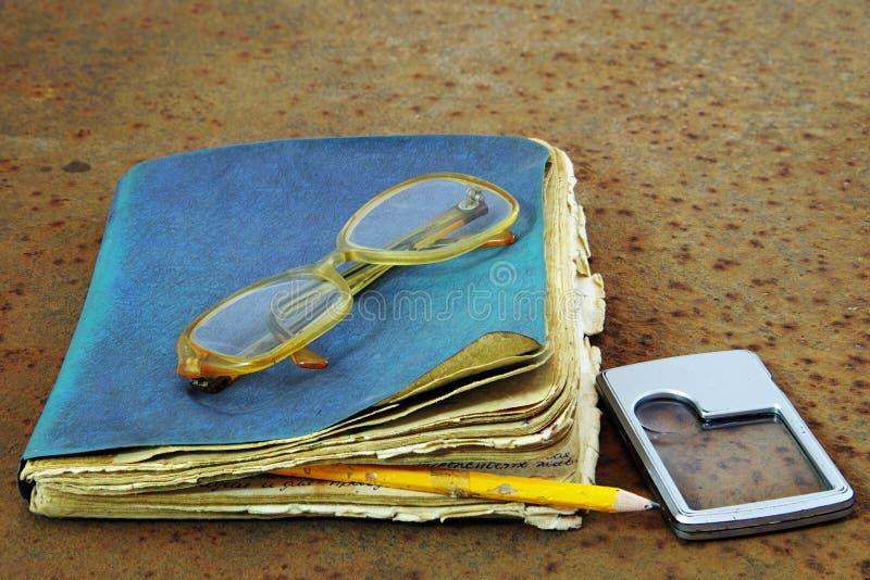 老笔记本、铅笔、玻璃和寸镜 免版税库存照片
