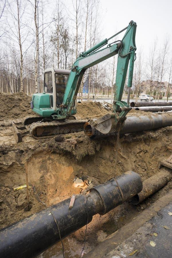 老管子的替换有新的,焊工在被挖掘的坑运作 免版税库存图片