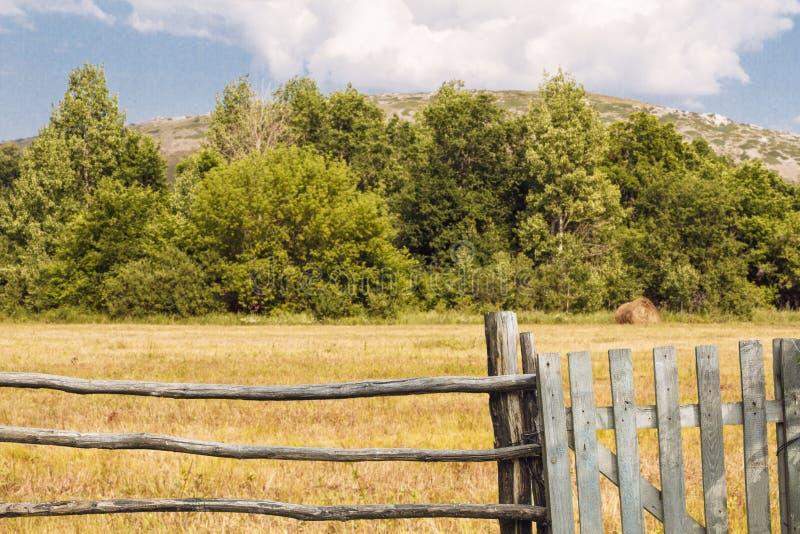 老篱芭由与门的木头制成在乡下 与森林和山的美好的夏天风景 土气生活方式概念 免版税库存照片