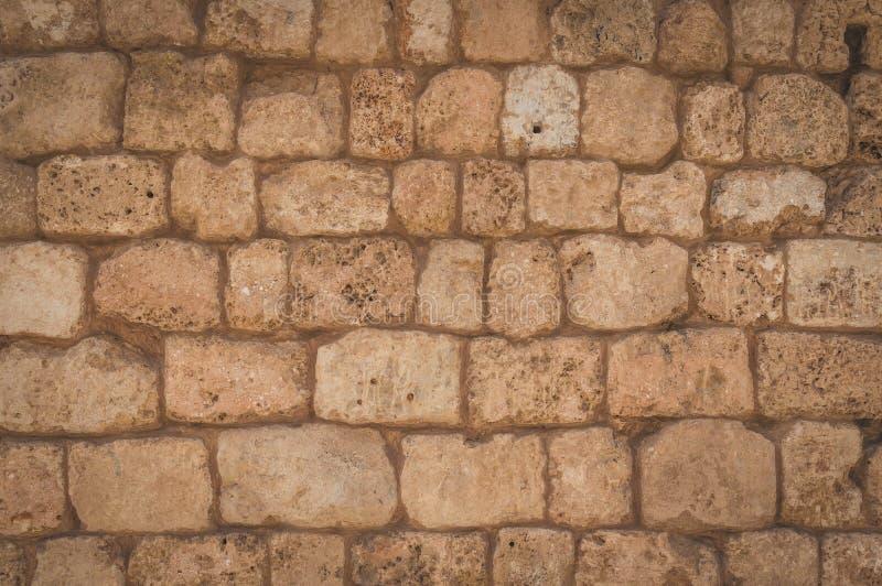 老米黄石墙背景纹理关闭 从在海附近的墙壁特拉维夫港的  免版税库存图片