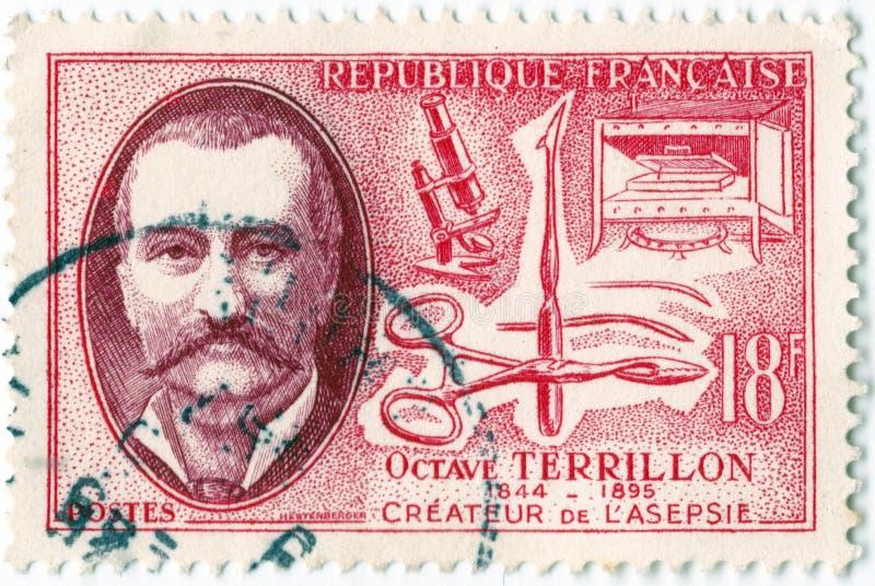 老红色法国邮票在1957年发布了与八音度terrillon的图象作早期工作在无菌手术的医师 免版税图库摄影