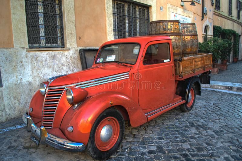 老红色葡萄酒汽车在罗马,意大利的中心 库存图片