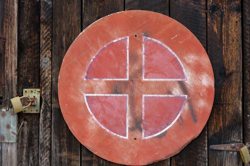 老红色风化了在木墙壁上的路牌 库存图片