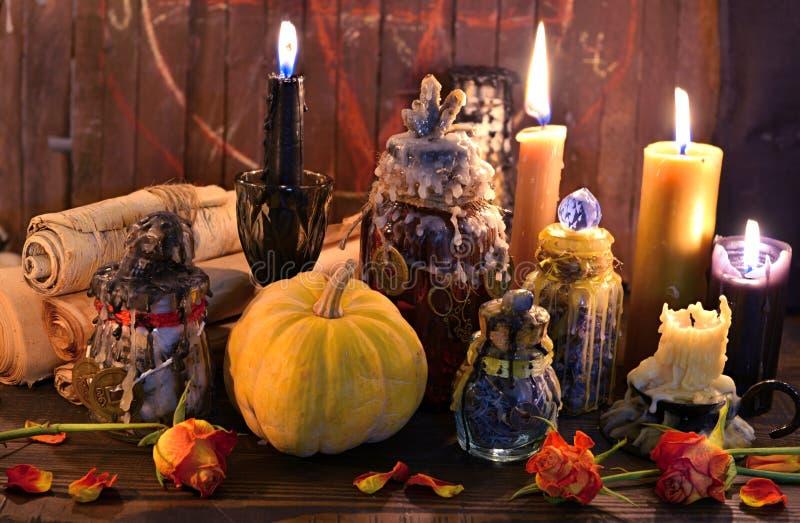 老纸纸卷、南瓜、蜡烛和不可思议的瓶在巫婆桌上 库存图片