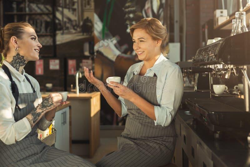 老练的分享经验的barista和她的学生 免版税库存照片