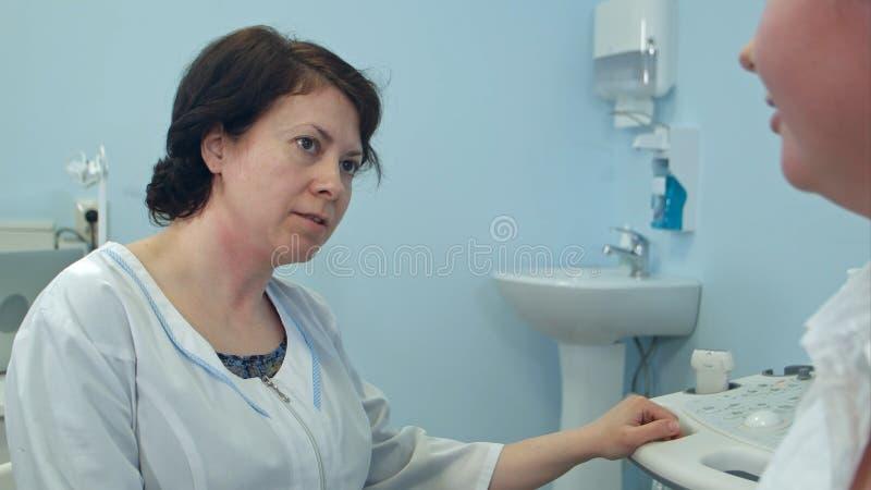 老练的女性医生谈话与患者在医院 免版税库存照片