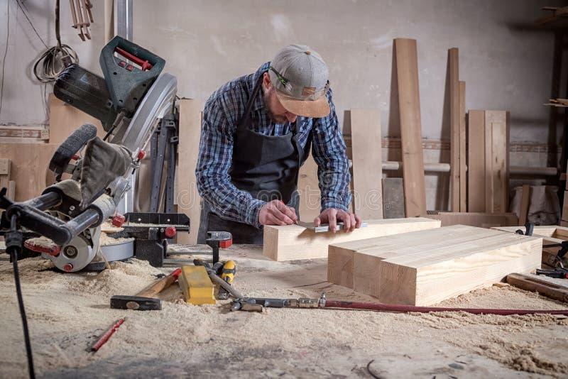 老练的木匠与木一起使用 库存照片