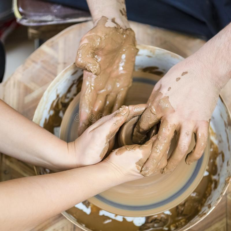 老练的男性陶瓷工的手特写镜头工作与女性学徒的 与在横式转盘的黏土团一起使用 免版税库存图片