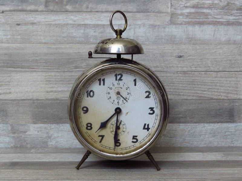 老经典时钟,时间,警报,葡萄酒,在被漂白的和白涂料山毛榉的木材背景的闹钟 库存图片