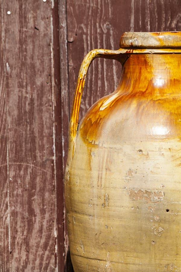老罐褐色赤土陶器瓶子 背景老难看的东西木头 图库摄影