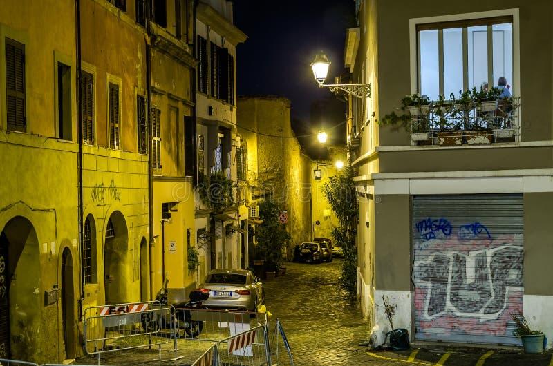 老罗马狭窄的街道,意大利夜与停放的汽车在他们和发光的灯笼和房子有点燃的窗口的 免版税库存图片