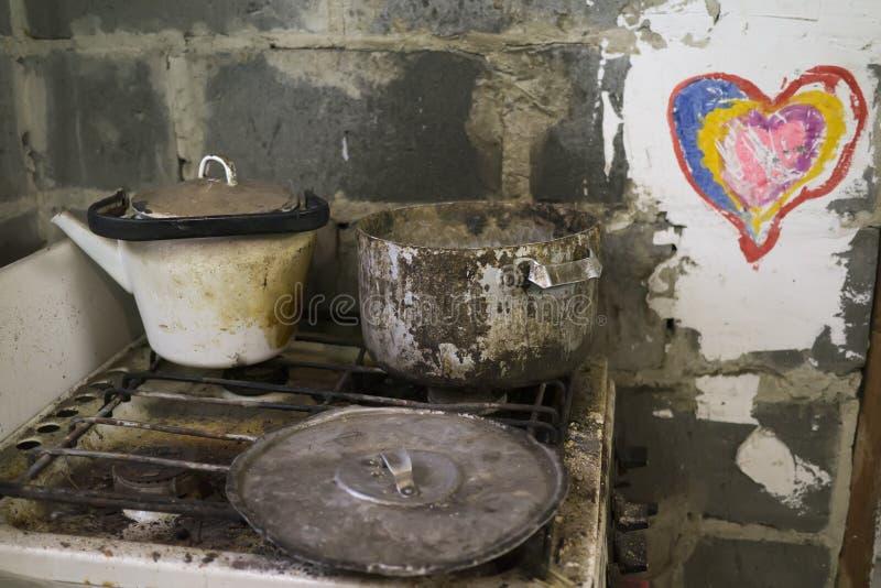 老肮脏的罐,水壶,在生锈的煤气炉的盖子 免版税图库摄影