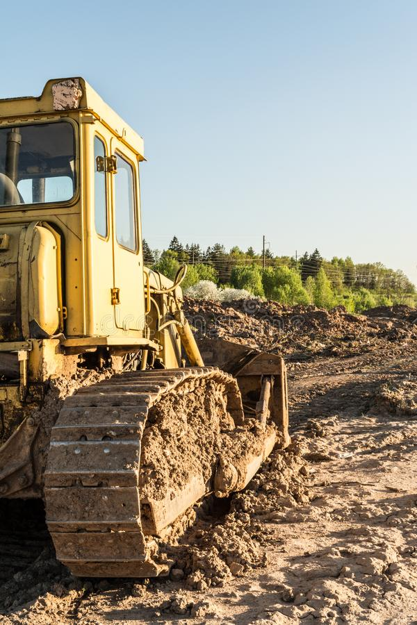 老肮脏的黄色履带牵引装置推土机,背面图,建筑机器由落日的光芒点燃 图库摄影
