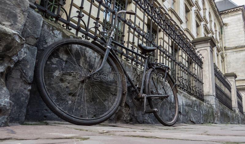 老自行车停放了反对篱芭和一个老房子 库存照片