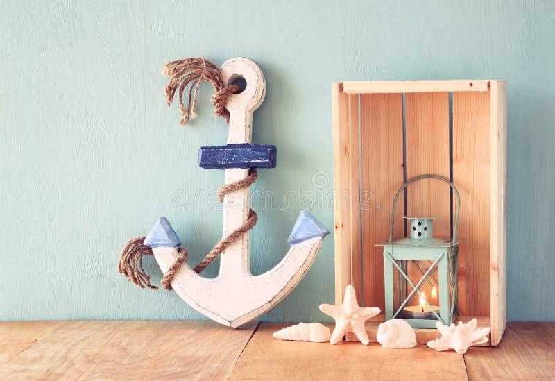 老船舶木船锚、灯笼和壳在木桌上在木水色背景 免版税库存图片