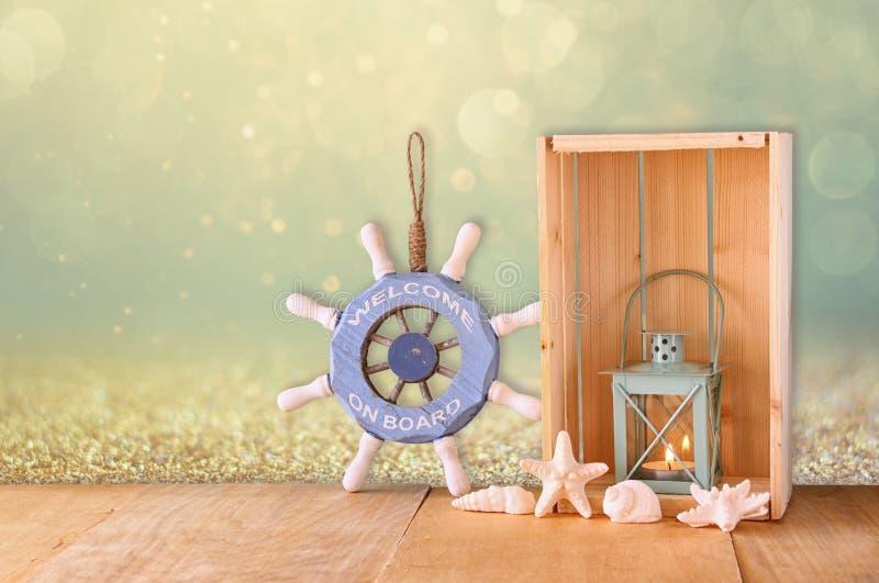 老船舶木轮子、灯笼和壳在木桌上在木闪烁背景 库存图片