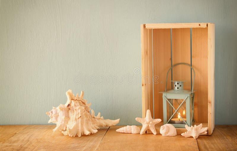 老船舶灯笼和壳在木桌上在木水色背景 库存照片
