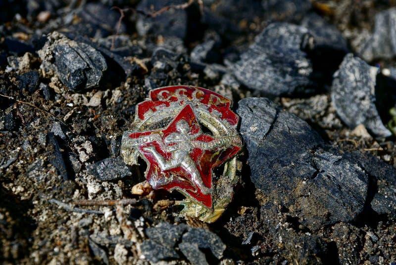 老苏联徽章在街道的地面上说谎 库存照片