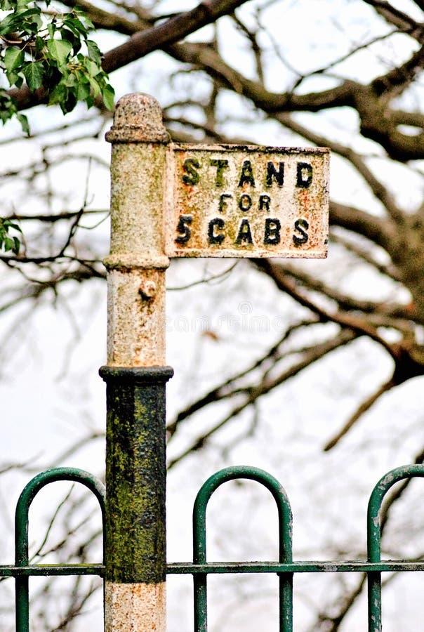 老英国森林地和锻铁操刀隔绝和包围的孤立出租汽车站 路过的时期的标志 库存图片